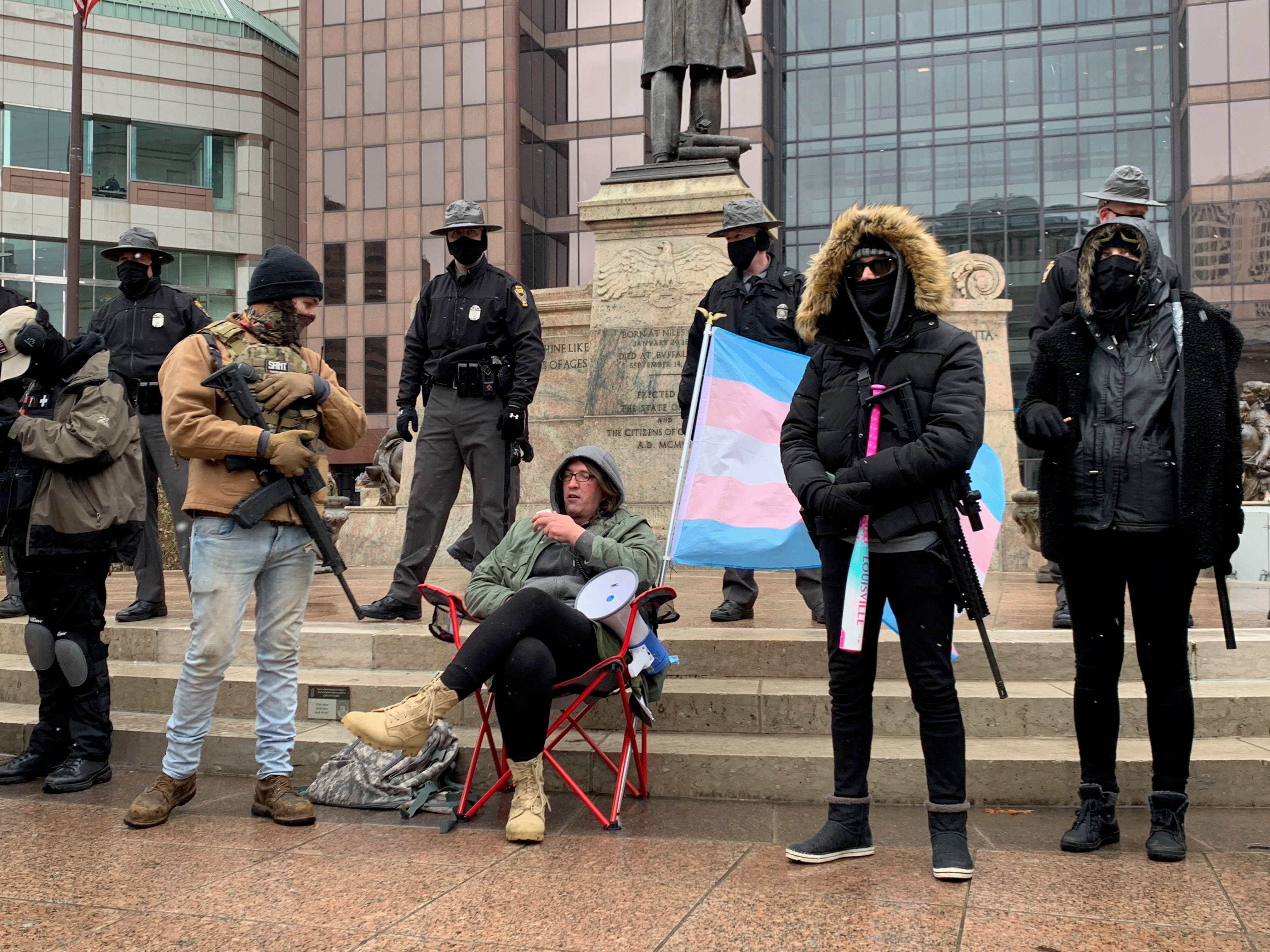 """Dan Werts of Logan County, Ohio, speaks into a megaphone while sitting in front of the Ohio Statehouse in a chair with the Trans Pride flag attached on Sunday, Jan. 17, 2021. """"Just a reminder, it was not antifa who raided the Capitol, it was Trump supporters,"""" Werts said. """"You have the audacity to try and rewrite history and make yourselves look like the good guys. That's pathetic."""""""