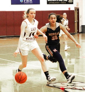 John Glenn senior Abi Shirer (14) dribbles up-court with Morgan's Heaven Williams (30) applying defensive pressure during Saturday afternoon's MVL match-up at John Glenn High School.