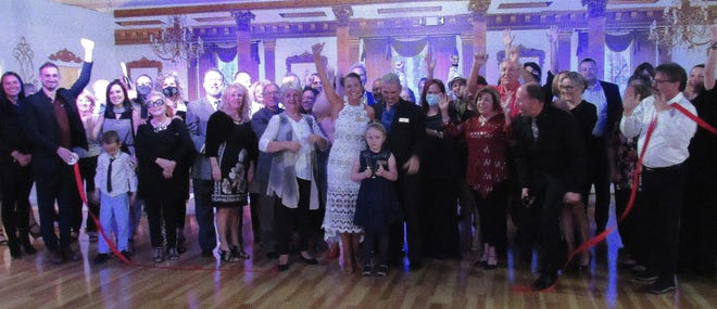 The crowd celebrates the ribbon-cutting for Elite Dance and Travel, led by owner Magdelena Piekarz on Friday night.