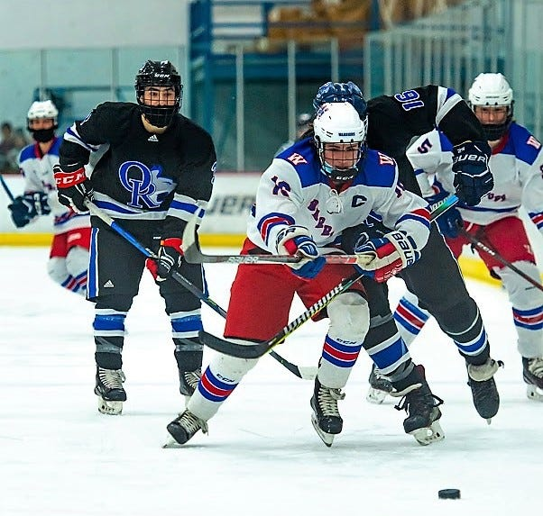Winnacunnet senior captain Jake Giacalone chases down the puck with Oyster River's AJ Bellabona, right, during Saturday's Division II boys hockey game at The Rinks at Exeter.