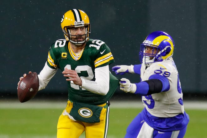 Green Bay Packers quarterback Aaron Rodgers (12) throws under pressure from Los Angeles Rams defensive tackle Aaron Donald (99) during the first half of an NFL divisional playoff game Saturday, Jan. 16, 2021, in Green Bay, Wis.