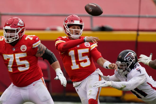 Kansas City Chiefs quarterback Patrick Mahomes throws a pass while being chased down by Atlanta Falcons Jacob Tuioti-Mariner during the second half of an NFL football game, Sunday, Dec. 27, 2020, in Kansas City.