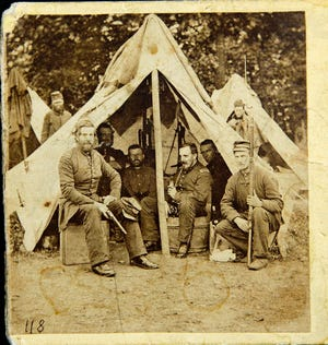 This family photo, made in June 1861, shows Dr. Bowman Bigelow Breed, right inside tent with pipe. Breed, who served as a surgeon in the Union Army during the Civil War, was a member of the 8th Massachusetts Volunteer Militia, which was bivouacked in the U.S. Capitol Rotunda in the early days of the war. [Courtesy of the Breed Family via AP]