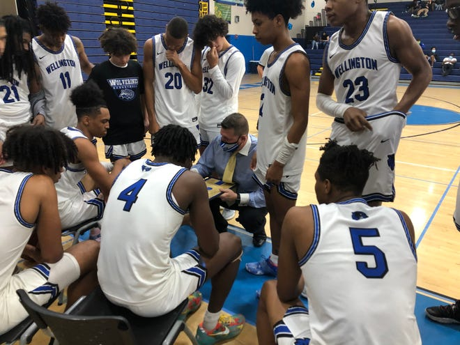 Wellington High coach Matt Colin discusses strategy with his team during Friday night's 57-54 victory over Palm Beach Central.