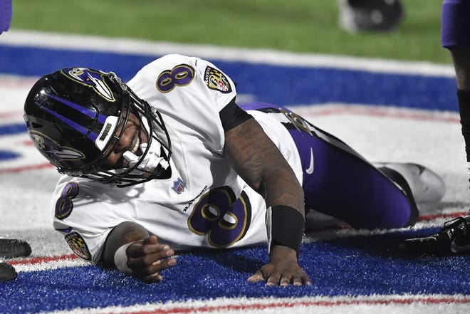 Ravens quarterback Lamar Jackson lies in the end zone in pain after being hit hard by Bills defensive lineman Trent Murphy and suffering a concussion during Saturday night's loss in Buffalo.