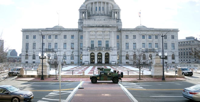 National Guard vehicles patrol along Smith Street in front of the Rhode Island State House with and state police State blocking plaza entrances Sunday morning.