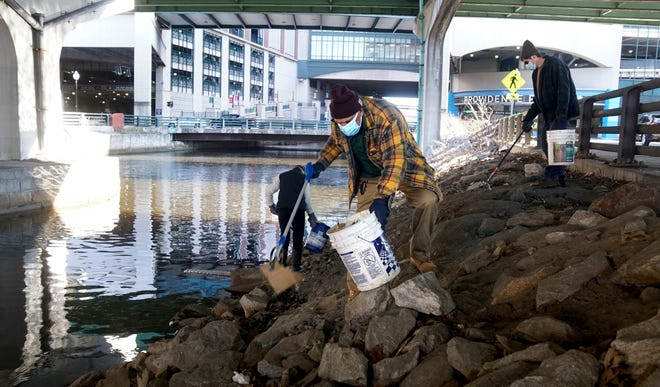 Steven Calise, of Providence, joins others under the Route 95 bridge helping clean up along the Woonasquatucket River behind Providence Place on Sunday morning. In conjunction with this week's inauguration of President Joe Biden and Vice President Kamala Harris, the Woonasquatucket River Watershed Council commits to a day of service honoring Dr. Martin Luther King Jr.
