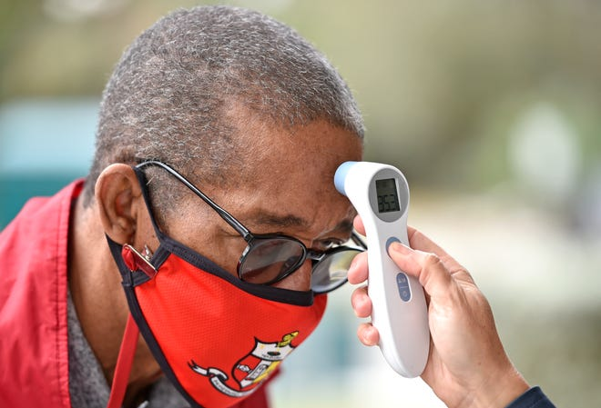 Henry Marsh, 72, gets his temperature taken before entering a vaccination clinic held at the Sarasota Memorial Internal Medicine building in Newtown in January.
