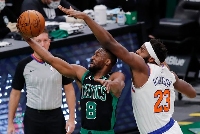 Boston Celtics' Kemba Walker (8) shoots against New York Knicks' Mitchell Robinson (23) during the first half of an NBA basketball game, Sunday, Jan. 17, 2021, in Boston.