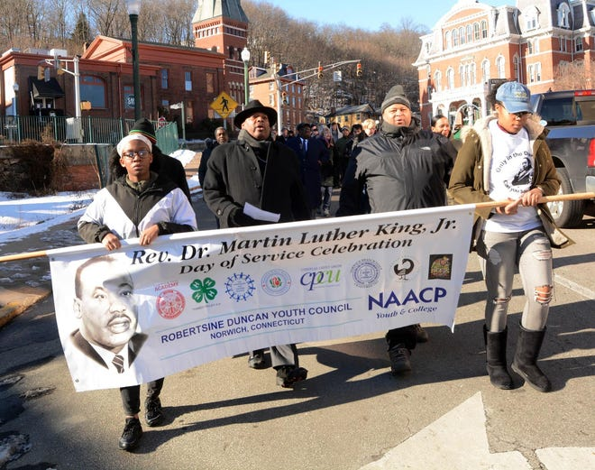 "From left, Thsarny Pierre, the Rev. John Gentry, Anthony Holland and Teala Avery lead others singing ""Lift Every Voice"" on Jan. 20, 2020, as they walk in downtown Norwich to Evans Memorial AME Zion Church on Martin Luther King Jr. Day in Norwich."