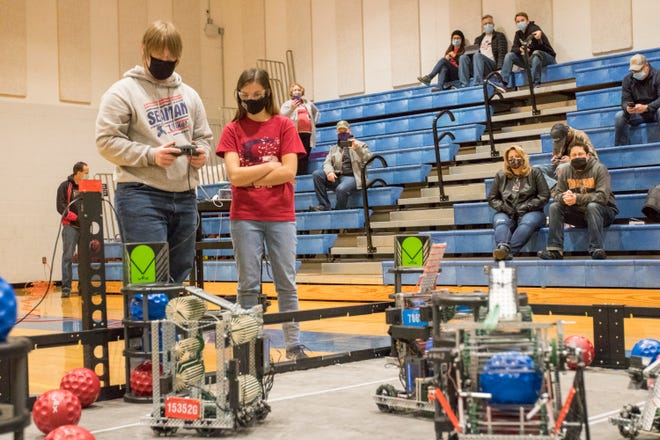 Eric Koon, the sophomore son of Seaman High robotics coach Donald Koon, drives his team's bot as teammate Emily Harmon, also a sophomore, watches on Saturday in the school's gym.