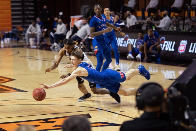 Kansas basketball guard Christian Braun, front, fights for a loose ball during last Tuesday's game against Oklahoma State in Stillwater, Okla. Braun scored seven points on 3-for-7 shooting in the Jayhawks' 75-70 defeat.