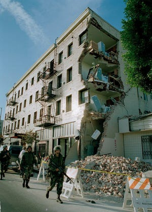 California National Guardsman walk past a Hollywood apartment building, damaged by a deadly earthquake on Hollywood Boulevard, near Normandie Avenue, Jan. 18, 1994. The 4th/160th Infantry Battalion stationed in San Diego was activated to help police prevent looting in homes and stores.