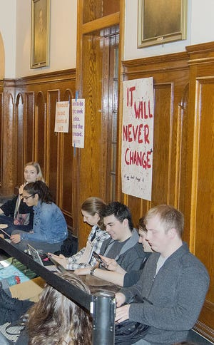 Holy Cross students sit inside Fenwick Hall during a 2019 protest.