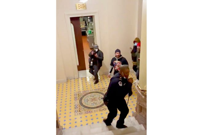 In this image made from video and provided by HuffPost, Capitol Police Officer Eugene Goodman calls for backup as an angry mob gives chase inside the U.S. Capitol in Washington on Jan. 6, 2021. One bright spot in all the chaos and anger from the mob siege at the U.S. Capitol was Goodman confronting a mob and retreating, risking his life to perhaps save the U.S. Senate. (Igor Bobic/HuffPost via AP)