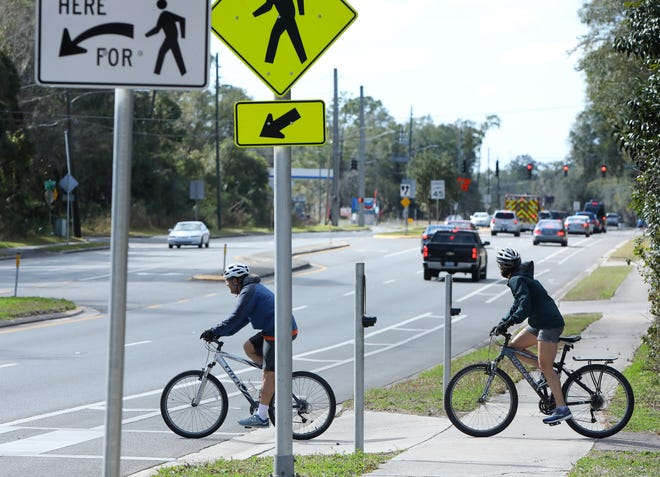 Cyclists cross Williston Road at the Hawthorne Trail crossing on Saturday in Gainesville. The crossing is notorious for its confusion to trail users and to motorists. Several crashes and near misses have occurred there. [Brad McClenny/The Gainesville Sun]
