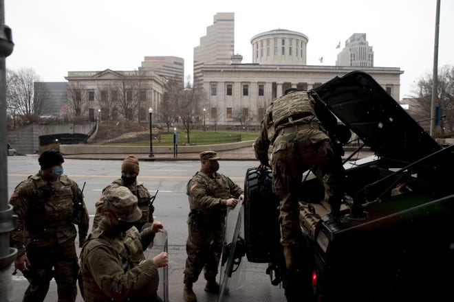 A National Guard member load riot gear into an armored vehicle in front of the Vern Riffe State Office Tower on Broad Street in Columbus, Ohio on January 17, 2021.