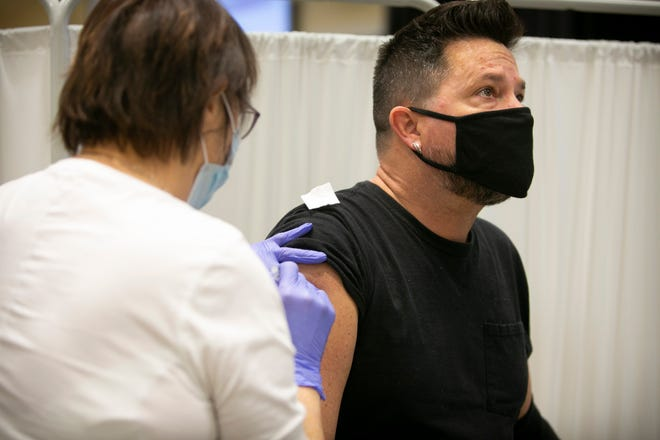 Rob McCoy, a seventh-grade teacher with Fort Thomas Independent Schools, receives his COVID-19 vaccination from registered nurse Mary Hogan, at St. Elizabeth Training & Education Center, in Erlanger, on Sunday, January 17, 2021.