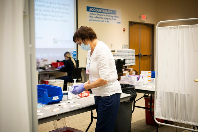 Registered nurse Mary Hogan organizes her station as she gives COVID-19 vaccines at St. Elizabeth Training & Education Center, in Erlanger, on Sunday, Jan. 17, 2021