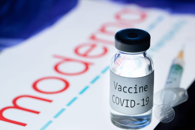 """This picture taken on November 18, 2020 shows a syringe and a bottle reading """"Vaccine Covid-19"""" next to the Moderna biotech company logo."""