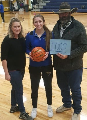 Augusta High School senior Olivia Isakson, center, scored her 1,000th career point Saturday in the Elks' 42-34 win over Power. She is flanked by her Mom Cari and Dad Broady.