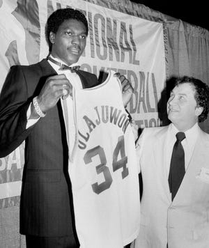Hakeem Olajuwon holds up his new jersey after being selected by the Houston Rockets in the NBA draft in New York, June 19, 1984. Rockets owner Charlie Thomas looks up at right. Olajuwon was the first person selected in the draft. (AP Photo/Marty Lederhandler)