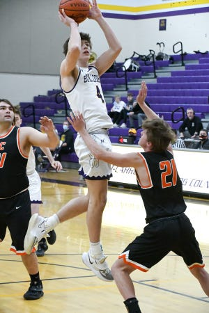 Bloom Carroll's Evan Dozer shoots the ball over Amanda-Clearcreek's Tayvon Miller Saturday night. The Bulldogs went on to defeat the visiting Aces, 52-28.