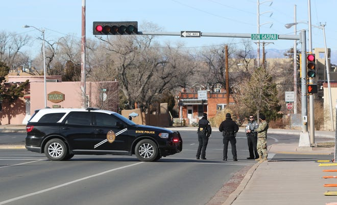 Law enforcement agencies, including New Mexico State Police and the Santa Fe County Sheriff's Office, as well as the New Mexico National Guard, stand watch near  the Roundhouse, New Mexico's capitol building in Santa Fe, on Sunday, Jan. 17, 2021. Expected protests did not materialize.