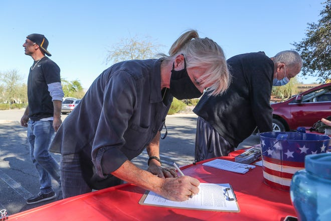 Deborah, left, and Mike Aiton sign a petition to recall Gov. Gavin Newsom outside Westfield Palm Desert, January 17, 2021.
