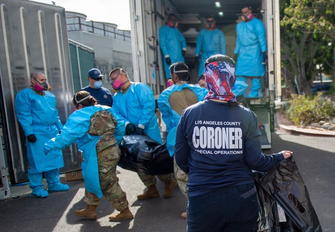 An L.A. County coroner's department employee works alongside National Guardsmen who were helping to process bodies of COVID-19 patients and put them into temporary storage in Los Angeles in January.
