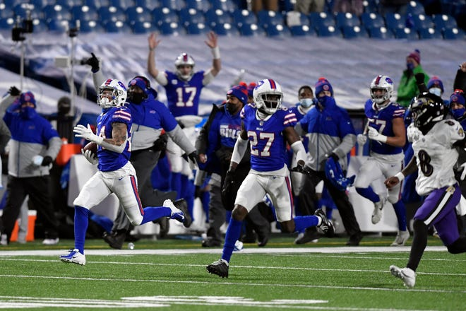 Buffalo Bills cornerback Taron Johnson, left, runs away from Baltimore Ravens quarterback Lamar Jackson (8) after intercepting his pass for a touchdown during the second half of an NFL divisional round football game Saturday, Jan. 16, 2021, in Orchard Park, N.Y.