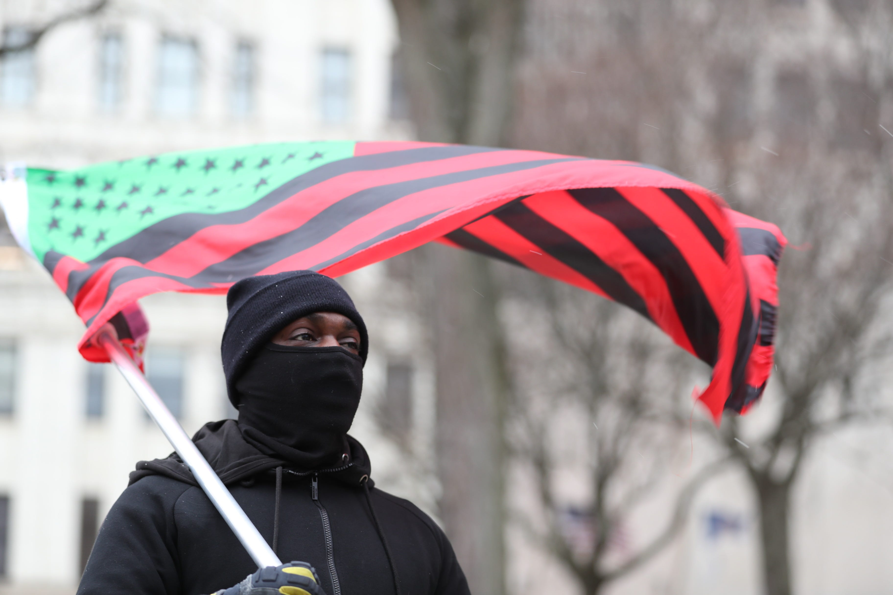 A man carries a Black liberation flag outside the New York state Capitol in Albany on Sunday, Jan. 17, 2021.