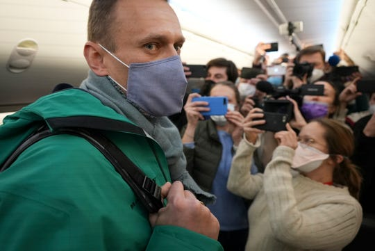 Alexei Navalny is surrounded by journalists inside the plane prior to his flight to Moscow from Berlin on Jan. 17, 2021.