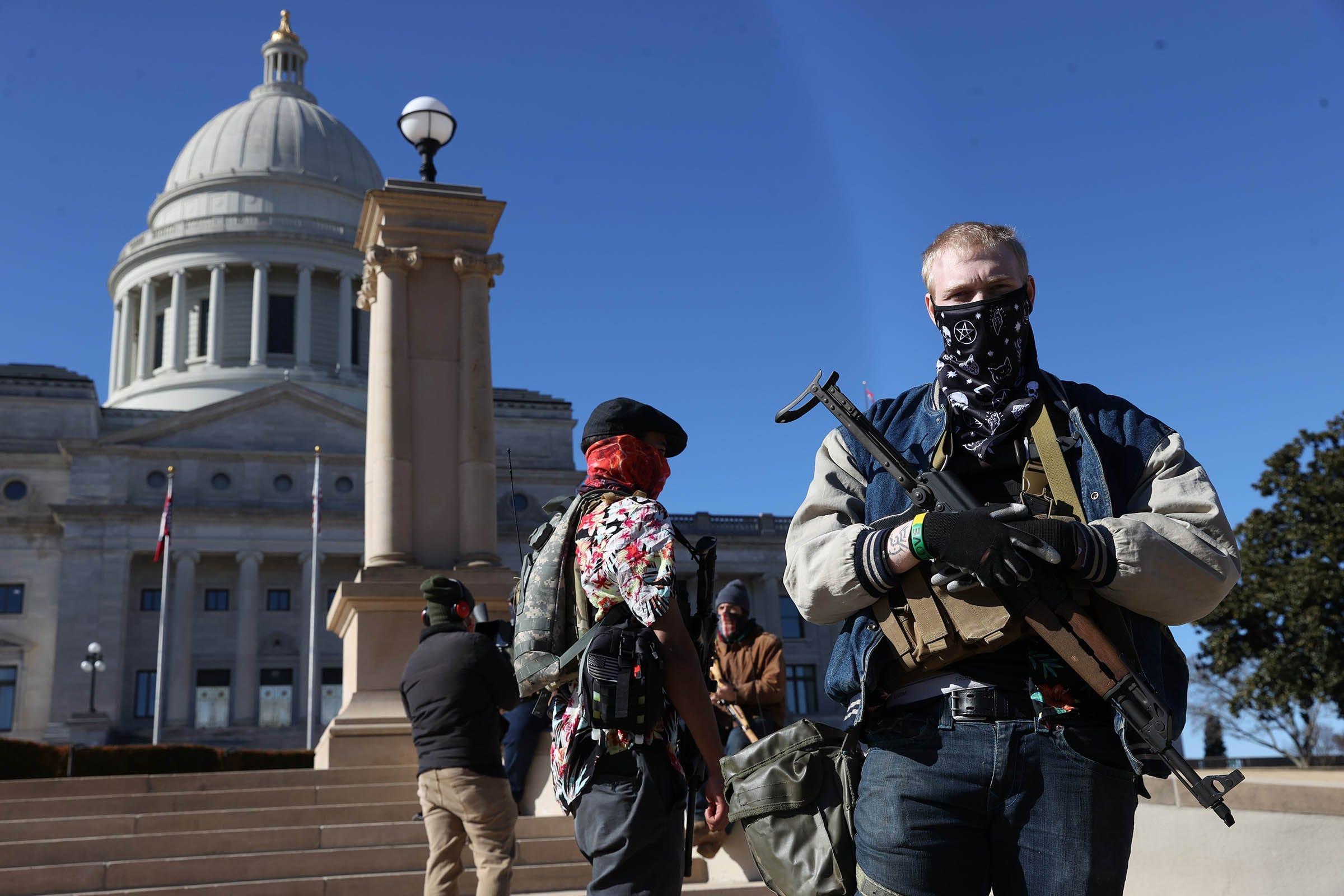 A man who only identified himself as Scott and a small group of armed protesters stand outside the Arkansas State Capitol on Jan. 17, 2021.