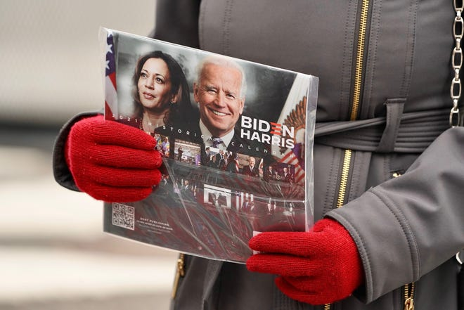 A customer holds a Biden-Harris calendar before buying it in Washington, DC, a few days before Inauguration Day. The nation's capital is on high-alert with heightened security against threats to President-elect Joe Biden's inauguration  following the deadly pro-Trump insurrection at the U.S. Capitol.