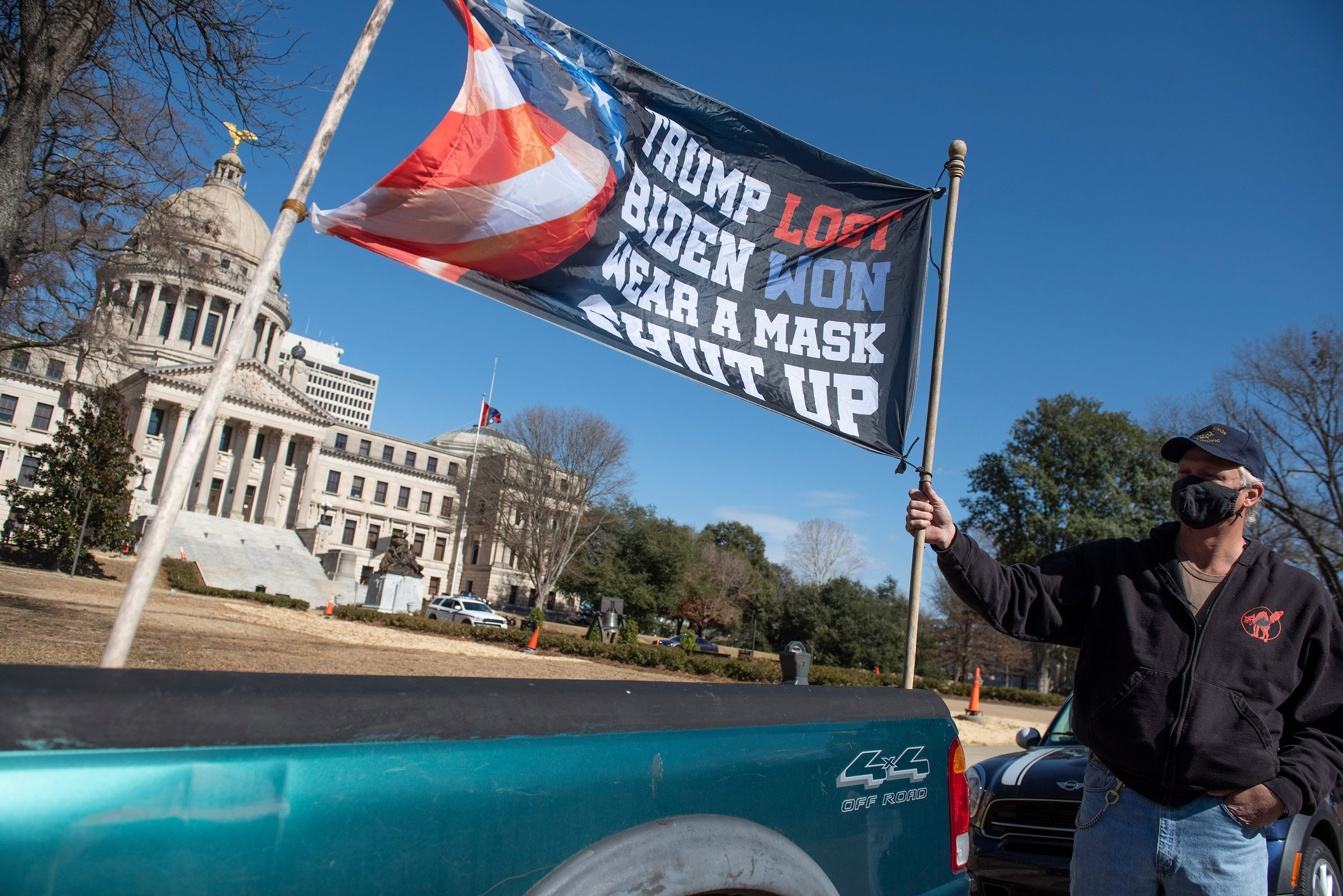 Dale Gibson, of Jackson, Miss., shows off the banner he planned to hold as a counter protester if a pro-Trump rally materialized, Sunday, Jan. 17, 2021, in Jackson. Visibly enhanced security surrounded the Mississippi State Capitol.