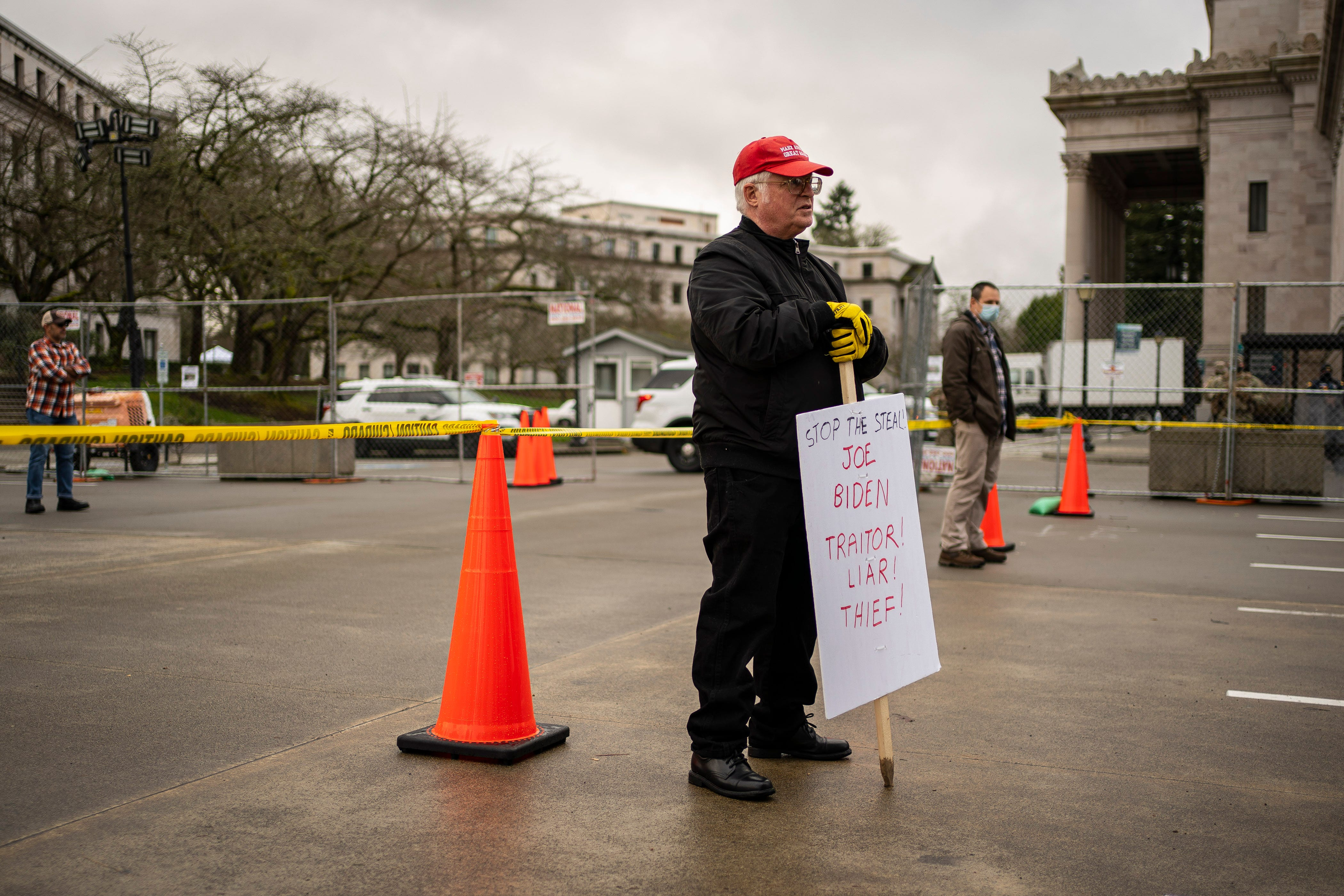 """A Trump supporter holds a sign that reads """"Stop The Steal! Joe Biden Traitor! Liar! Thief!"""" in front of the Washington State Capitol on Sunday, Jan. 17, 2021, in Olympia, Washington."""