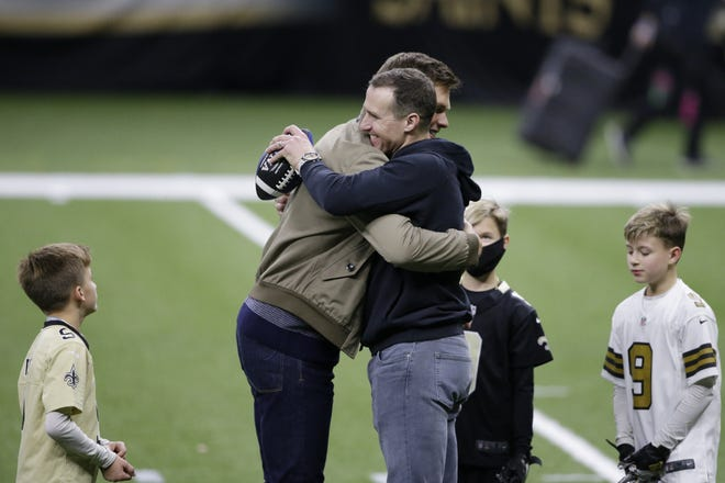 New Orleans Saints quarterback Drew Brees right, embraces Tampa Bay Buccaneers quarterback Tom Brady after Sunday's NFL divisional playoff game. The Saints lost 30-20, and Brees, 42, is contemplating retirement.