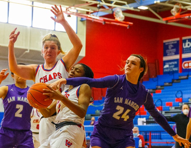 Westlake Chaparrals guard LaQuayla Chambers-Wells, center, battles for the ball with San Marcos forward Faith Phillips, right, as teammates Gwen Gilmore comes in to help. Chambers-Wells and Gilmore helped Westlake edge the Rattlers 54-53 Saturday at Westlake High School to remain perfect in District 26-6A.