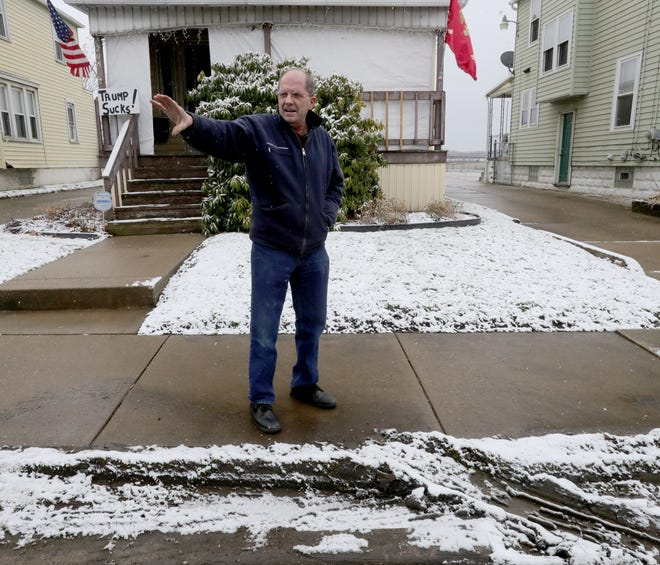 East Voris Street resident John Sopko points out damage to the devil strip and sidewalk from mail trucks positioning for queue at the Wolf Ledges Post Office in Akron.