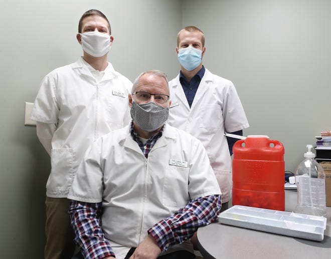 Pharmacist Tom Lamb and two of his partners, pharmacists Jason Sloan and Robert Nearhoof, gather Monday in one of the two vaccination rooms at Sand Run Pharmacy in Akron.