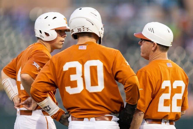 Texas coach David Pierce (22) speaks with runners Eric Kennedy (30) and Silas Ardoin during a game against Abilene Christian on Mach 11, 2020. D1Baseball has voted Texas into the ninth slot of its preseason poll for the 2021 season.