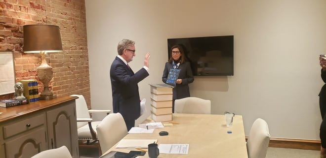 Ardmore attorney Michael C. Mordy takes the oath of office to become president of the Oklahoma Bar Association as his wife Christy looks on. Friday's ceremony was the first time the OBA held a virtual ceremony, and Mordy was sworn in from his office in Ardmore.