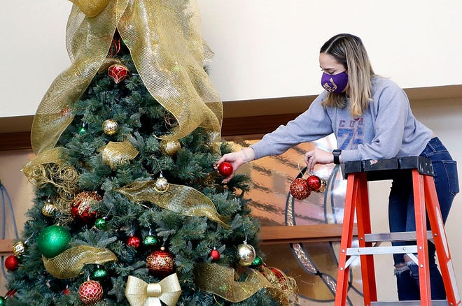 Ashland University student Brittany Wressell, a member of AU G.I.V.S., removes the Christmas ornaments at the Kroc Center as a part of the group's Martin Luthern King Day community service projects on Monday. Students also served at an ACCESS housing complex, Ashland County Cancer Association, Ashland Pregnancy Care Center and Safe Haven. TOM E. PUSKAR/TIMES-GAZETTE.COM