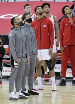 Injured Ohio State Buckeyes guards CJ Walker (13) and  Jimmy Sotos (1) watch the video screen before team introductions at Wednesday's NCAA Division I basketball game against the Northwestern Wildcats at Value City Arena in Columbus, Oh., on Wednesday, January 13, 2021.