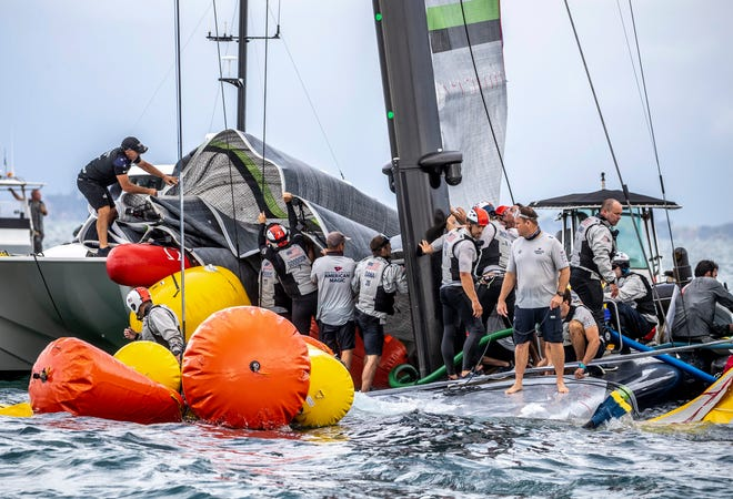 Crew from the United States' American Magic boat Patriot and Team New Zealand attempt to keep Patriot afloat after it capsized during its race against Italy's Luna Rossa on the third day of the America's Cup challenger series on Sunday.