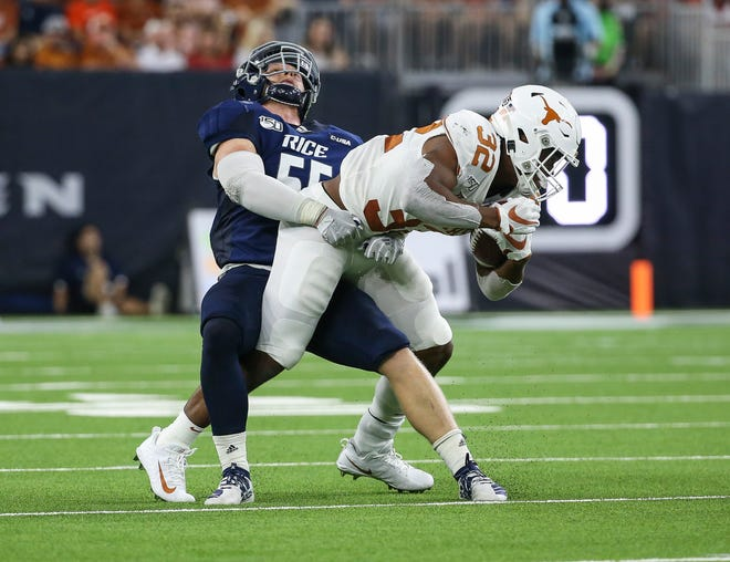 Rice linebacker Blaze Alldredge (55) attempts to tackle Texas running back Daniel Young (32) during a game Sept. 14, 2019, at NRG Stadium in Houston.