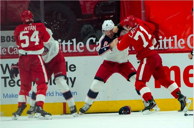 Detroit Red Wings center Dylan Larkin (71) punches the Blue Jackets' Zach Werenski (8), as Bobby Ryan (54) fights Blue Jackets right wing Oliver Bjorkstrand late in the third period Monday in Detroit. (AP Photo/Paul Sancya)