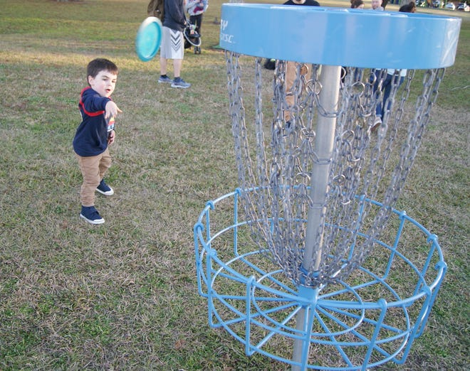 Miles Daigle, 2, throws a disc at the target at the disc golf course in Summerfield Park in Houma.