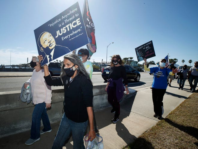 People participate in the Building Bridges Rather Than Barriers Dr. Martin Luther King Day march Monday in Port Orange.